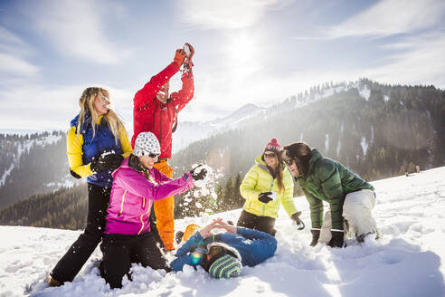 Group of carefree friends having fun in snow, Achenkirch, Austria - DHEF00291