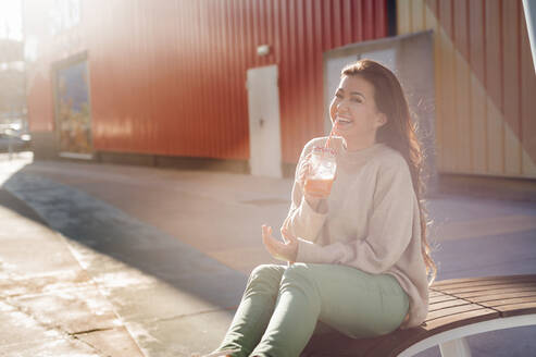 Cheerful young woman enjoying her drink while sitting on bench against shopping mall - JMPF00321