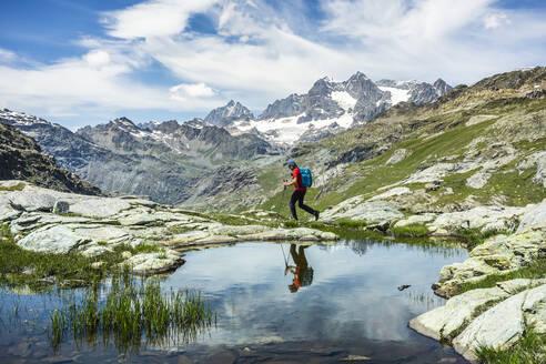 Man exploring while walking by lake at Western Rhaetian Alps, Sondrio, Italy - MCVF00572