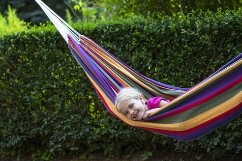 Smiling girl relaxing in colorful hammock at garden - JFEF00962