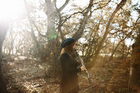 Young redhead woman playing clarinet while practicing in forest - MRRF00260