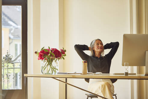 Businesswoman with hands behind head looking up at home office - MCF01056