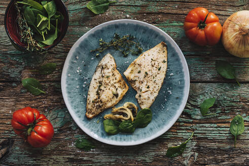 From above roasted fish with basil placed on shabby wooden table near fresh tomatoes and onion - ADSF10970
