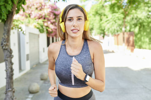 Woman listening to music while running outdoors - KIJF03211