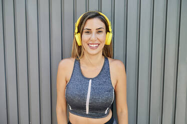 Smiling woman listening to music while standing against wall - KIJF03214