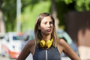 Woman with headphones standing in city - KIJF03217