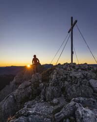 Rear view of hiker standing on viewpoint during sunrise, Gimpel, Tyrol, Austria - MALF00060