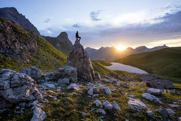 Hiker sitting on rock during sunset at Lake Rappensee, Bavaria, Germany - MALF00069