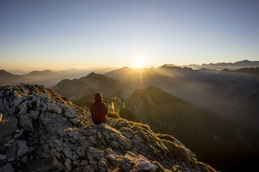 Female hiker sitting on viewpoint during sunset, Hochplatte, Bavaria, Germany - MALF00081