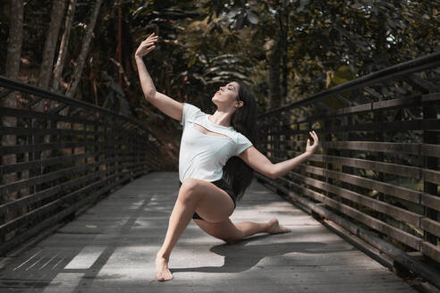 Full body barefoot female with outstretched arms and closed eyes dancing on wooden bridge on sunny day in peaceful garden - ADSF11047