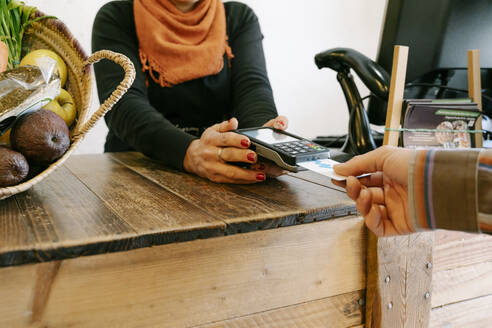 Female cashier assisting customer in payment through credit card at checkout in store - RDGF00058