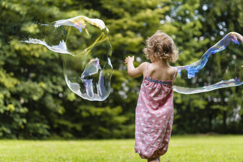Girl playing with bubbles at park - DIGF12910