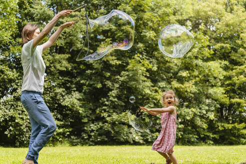 Happy daughter exploding bubble with mother at park - DIGF12913