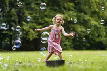 Smiling girl running amidst bubbles at park - DIGF12916