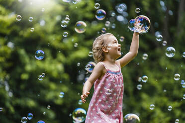 Cheerful girl amidst bubbles at park - DIGF12919