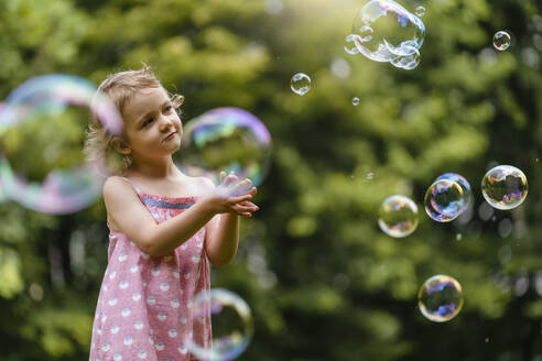 Cute girl looking at bubbles while standing in park - DIGF12922