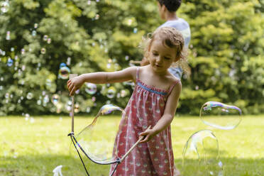 Cute baby girl making bubble with brother in background at park - DIGF12925