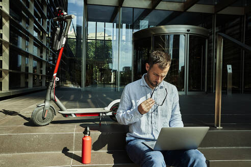 Entrepreneur with eyeglasses working over laptop while sitting on staircase - VEGF02742