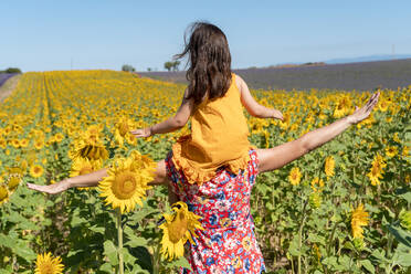 Mother carrying daughter on shoulders in sunflower field during summer - GEMF04085