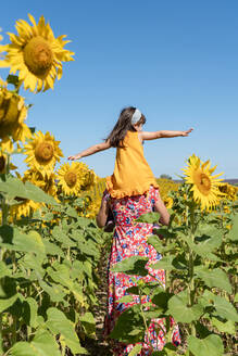 Mother carrying daughter on shoulders in sunflower field against clear blue sky - GEMF04088