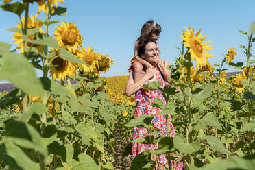 Smiling mother carrying daughter on shoulders in sunflower field during summer - GEMF04091