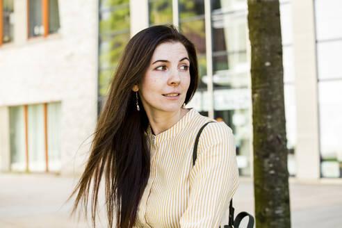 Portrait of brunette woman looking sideways in city - IHF00392