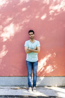 Man with arms crossed standing against wall - AFVF06906