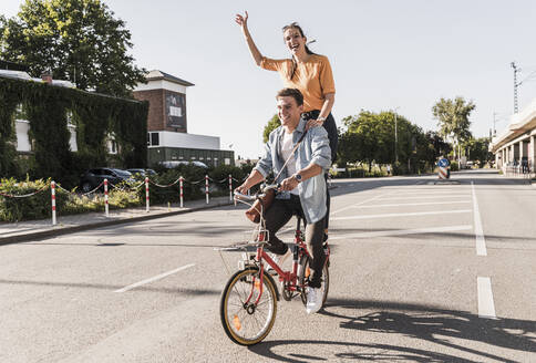 Cheerful young woman standing behind boyfriend riding bicycle on street - UUF20878