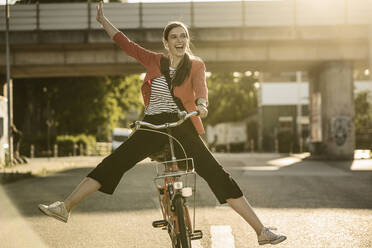Cheerful woman enjoying cycling on street in city during sunny day - UUF20935