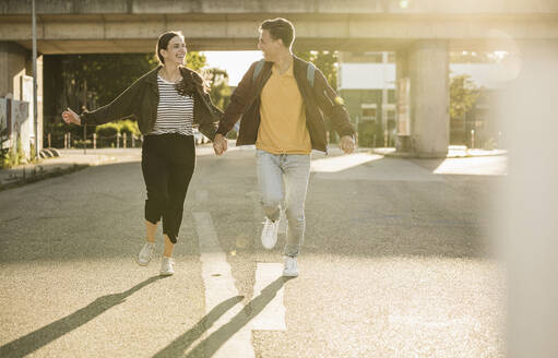 Carefree young couple holding hands while running on street in city - UUF20938