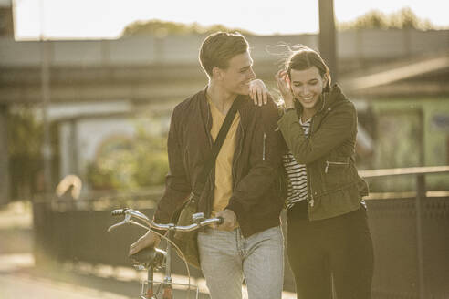 Happy couple with bicycle walking on street during sunny day - UUF20944