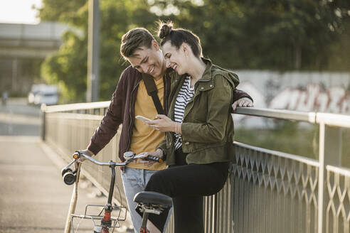 Smiling boyfriend and girlfriend looking at smart phone while standing with bicycle in city - UUF20953