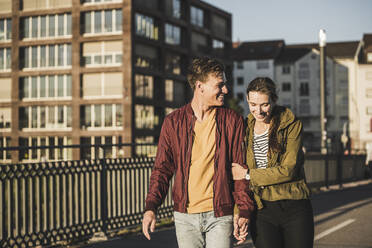 Smiling young couple holding hands while walking in city - UUF20956
