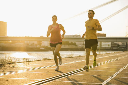 Smiling male and female jogging at harbor during sunny day - UUF20965