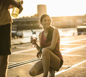 Smiling woman with friend holding water bottle while crouching outdoors - UUF20968