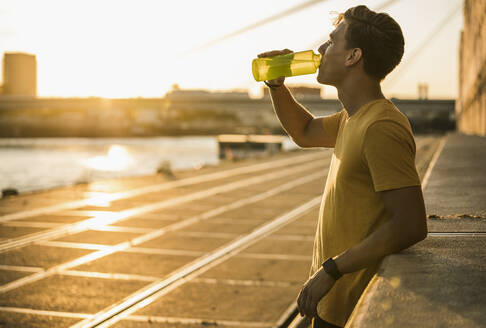 Man drinking water after workout against clear sky - UUF20971