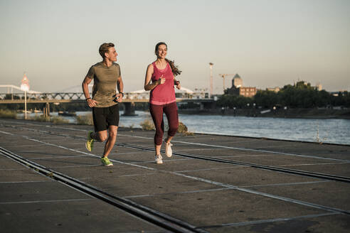 Male and female running at harbor - UUF20977