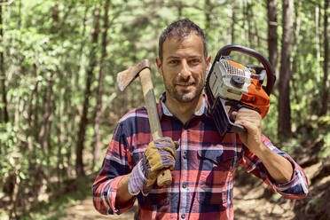 Smiling lumberjack standing with axe and chainsaw in forest - VEGF02780