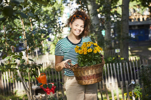 Smiling young woman holding basket with yellow flowers while standing in back yard garden - FMKF06282