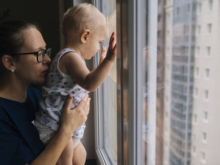 Mother holding baby boy looking through window at home - KNTF05194