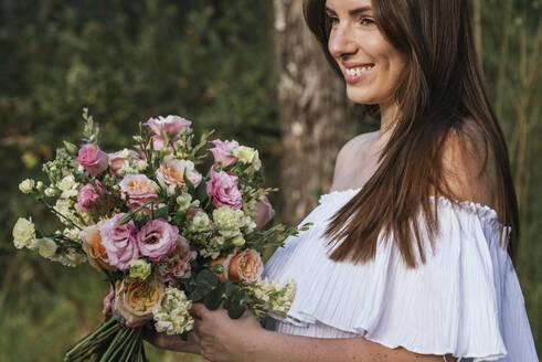 Smiling beautiful woman holding fresh flower bouquet - DSIF00094