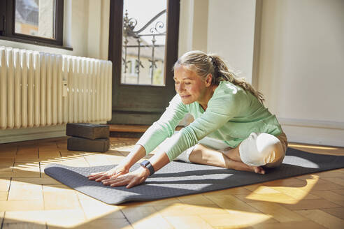 Woman exercising while sitting on exercise mat over floor in living room - MCF01167