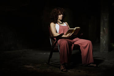 Woman sitting on chair while reading book at dark room - VEGF02783