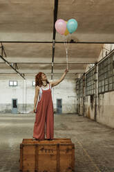 Woman standing on wooden box while holding colorful helium balloons - VEGF02786