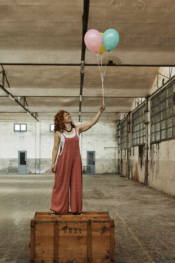 Woman standing on wooden box while holding colorful helium balloons - VEGF02786 - Veam/Westend61