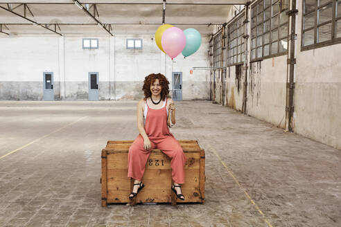 Smiling woman sitting on wooden box while holding colorful helium balloons - VEGF02789