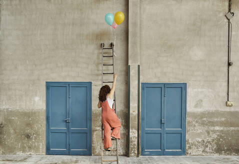 Woman climbing ladder leaning on wall while reaching for colorful helium balloons - VEGF02792