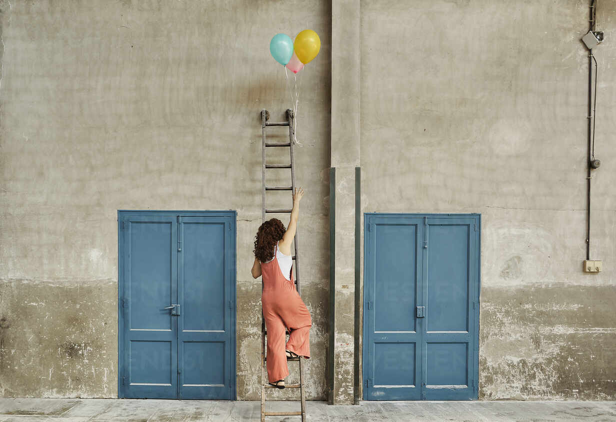 Woman climbing ladder leaning on wall while reaching for colorful helium balloons - VEGF02792 - Veam/Westend61