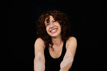 Smiling woman with white dust on arms against black background  - VEGF02798