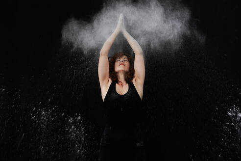 Woman clapping over head with white dust against black background - VEGF02801